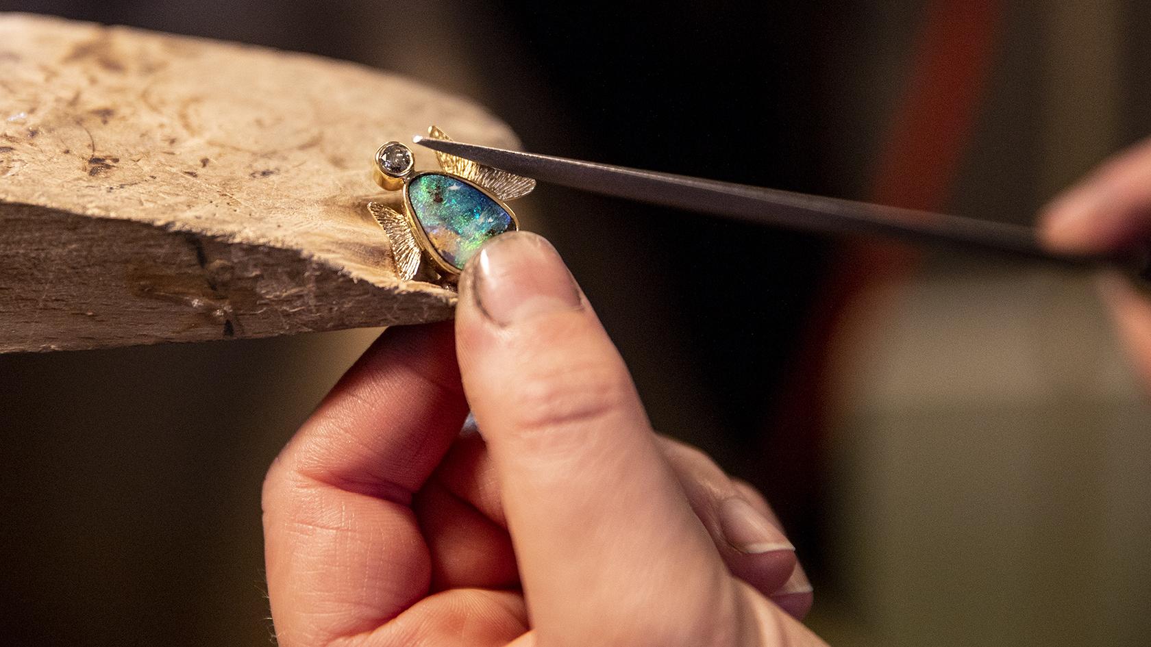 Englen er et af de nyeste unikasmykker, som Camilla Jensen har fundet på i samarbejde med sin chef og læremester. Smykket består af en australsk opal som englens krop, en diamant som hoved og små rillede guldvinger.